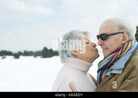 Senior couple standing face to face, kissing, side view - Stock Photo