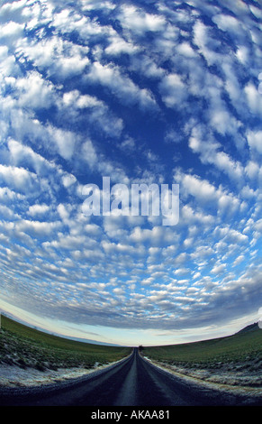 Altocumulus Clouds above a country road - Stock Photo