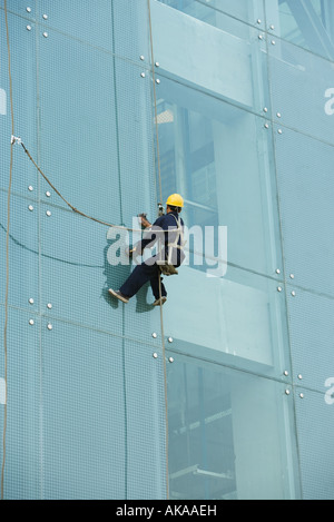 Window washer on side of office building, close-up - Stock Photo
