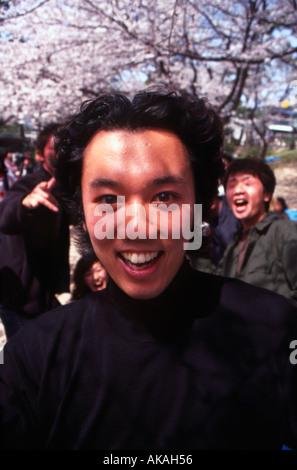 Teenage boy at cherry blossom party Japan - Stock Photo