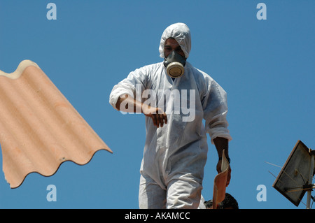 Israeli worker wearing protective mask remove asbestos roof tiles of evacuated Jewish settler house in Neve Dekalim - Stock Photo