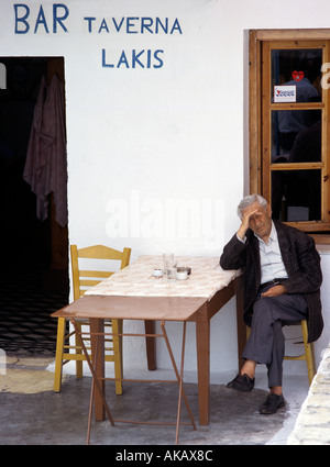 Old man relaxing sitting on chair leaning on a table outside bar in Lakis Greece Mediterranean Europe - Stock Photo
