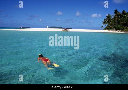 Woman wearing red bikini snorkelling alone in crystal clear tropical waters Tonga Pacific Ocean - Stock Photo