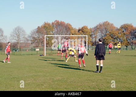 Back view of football referee controlling teenage boys playing football match wearing proper team kit Brentwood - Stock Photo