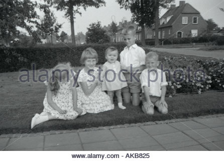 Girls and boys posing for a family picture 1960 s - Stock Photo