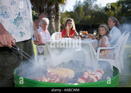 Man grilling, other family members sitting at table in background, close-up - Stock Photo