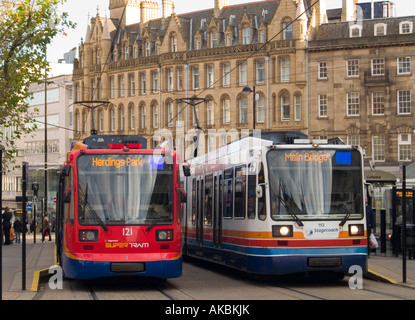 Two trams parked side by side in the Church Street area of Sheffield City Centre, UK
