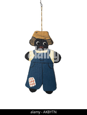 vintage Christmas ornament decoration of black boy dressed in overalls and straw hat hanging on hook - Stock Photo
