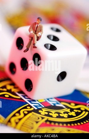 Tiny male figure in business suit sitting on dice and playing cards - Stock Photo