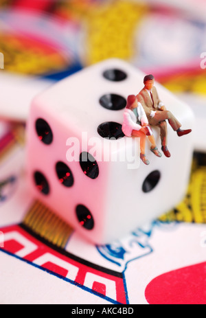 Male and female figures sitting on dice and playing cards - Stock Photo