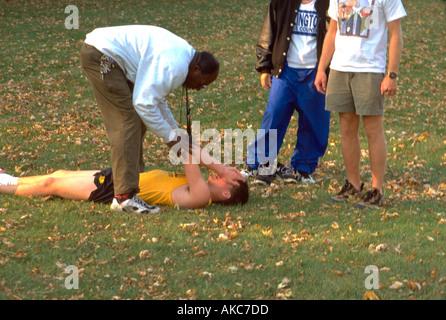 Coach 41 helping injured runner 16 at cross-country regional's. St Paul Minnesota USA - Stock Photo