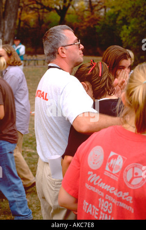 Coach consoling crying runner after losing race age 40 and 16. St Paul Minnesota USA - Stock Photo