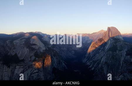 High resolution panorama of Yosemite valley shrouded by the evening gloom with Half Dome lit by the setting sun - Stock Photo
