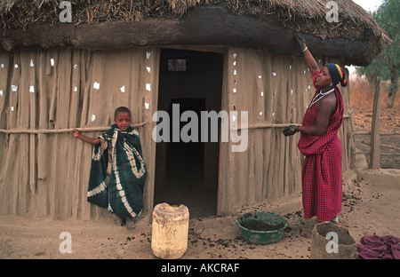 Masai woman plastering entrance and walls of her home with mud and ceramic fragments N of Arusha en route to S Kenya - Stock Photo