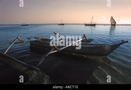 Passenger dhow ferrying people from Chole island to neighbouring Mafia island silhouetted against the rising sun - Stock Photo