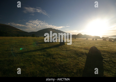 A Stock Photograph of sunrise over the mountains in the Lake District with castlerigg stone circle in the foreground - Stock Photo