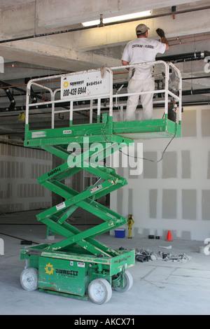 Miami Beach Florida Collins Avenue rental construction lift plumber working retail building - Stock Photo