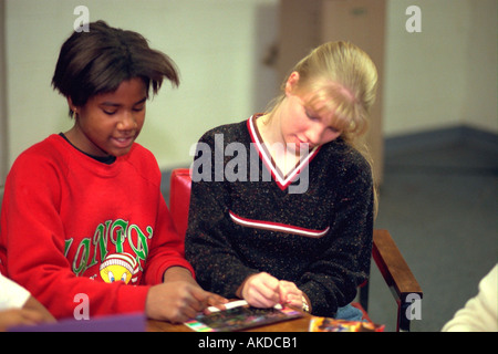 ethnically diverse teen girls age 14 coloring together at community youth center. St Paul Minnesota USA - Stock Photo