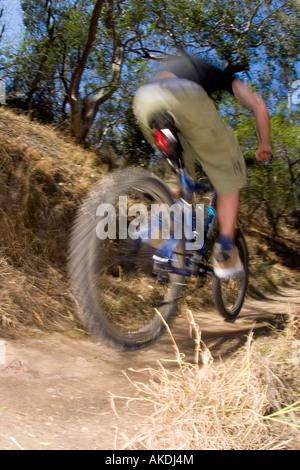 Riding a mountain bike through the bush fast. - Stock Photo