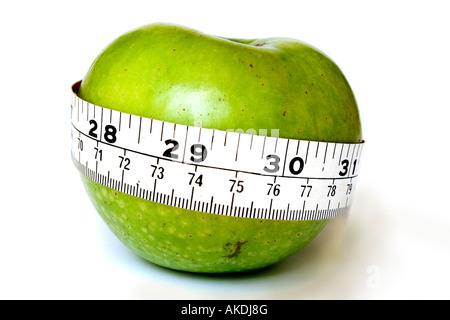 A stock photograph of an apple with a measuring tape around it. - Stock Photo
