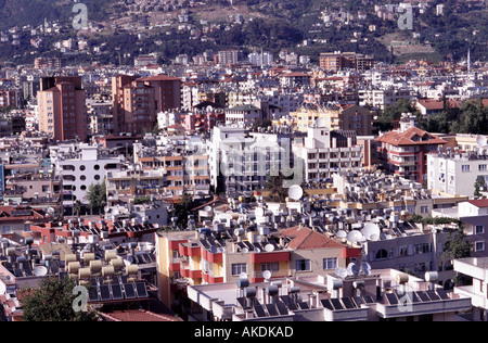 Alanya Turkey city view of buildings and roofs with solar panels for heating satellite dishes and water tanks - Stock Photo