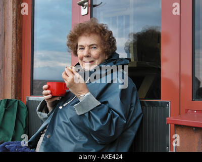 Margit 81 years old enjoying coffe and sandwiches on top of mountain north of Sweden - Stock Photo