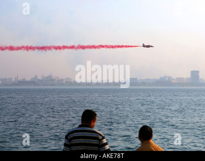 Expatriate workers watch as a member of the Red Arrows RAF display team flies in front of Qatar s Emiri Diwan (ruler's - Stock Photo