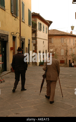 Rear view of two men walking in the street, Radda in Chianti Tuscany Italy - Stock Photo