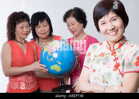Portrait of a mature woman smiling with her friends looking at a globe - Stock Photo