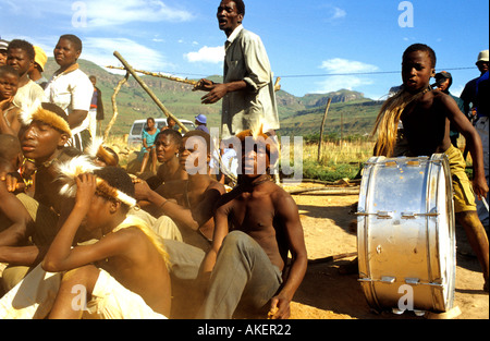 A group of men watch while a boy plays the drums during the traditional Zulu dancing festival - Stock Photo