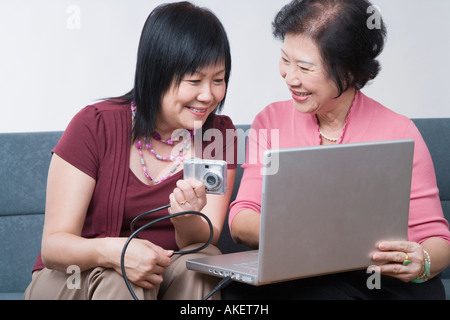 Close-up of a mature woman and a senior woman sitting with a digital camera connected to a laptop - Stock Photo