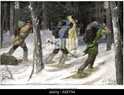 Native American trappers carrying furs on snowshoes in a forest of the Pacific Northwest - Stock Photo