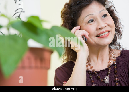 Close-up of a senior woman using a mobile phone and smiling - Stock Photo