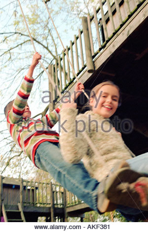 Kids playing on a swing - Stock Photo