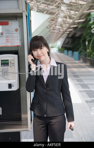 Portrait of a businesswoman talking on a public phone at an airport - Stock Photo