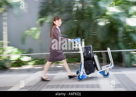 Side profile of a woman pushing a luggage cart - Stock Photo