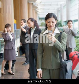 Businesswoman looking at a mobile phone at an airport - Stock Photo