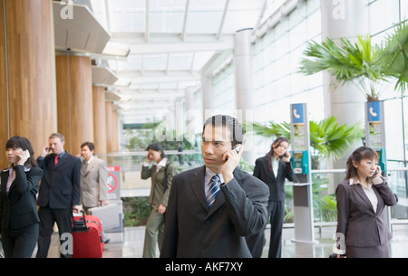 Business executives talking on mobile phones and leaving an airport lounge - Stock Photo