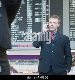 Businessman standing at an airport talking on a mobile phone - Stock Photo