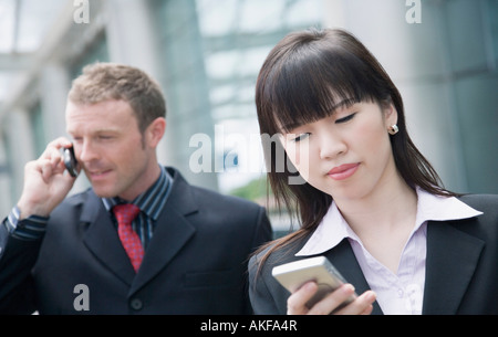 Close-up of a businesswoman using a personal data assistant with a businessman talking on a mobile phone behind - Stock Photo