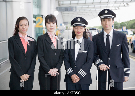 Portrait of a male and a female pilot standing with two cabin crew members - Stock Photo