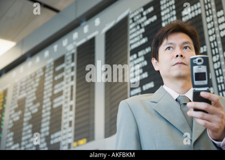 Close-up of a businessman at an airport holding a mobile phone - Stock Photo