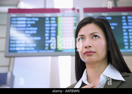 Low angle view of a businesswoman in front of an arrival departure board - Stock Photo
