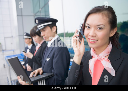 Portrait of a female cabin crew talking on a mobile phone with a pilot using a laptop in the background - Stock Photo