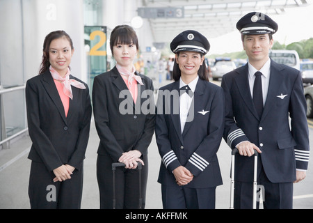 Portrait of two pilots standing with two cabin crews - Stock Photo