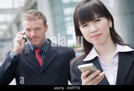 Close-up of a businesswoman holding a personal data assistant with a businessman talking on a mobile phone behind - Stock Photo