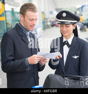Businessman showing an airplane ticket to a female pilot - Stock Photo
