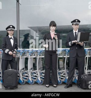 Female cabin crew standing with two pilots at an airport - Stock Photo