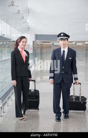 Male pilot and a female cabin crew walking and carrying their luggage in the corridor of an airport - Stock Photo