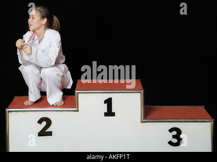 Young woman sitting on a winners podium with her medal - Stock Photo